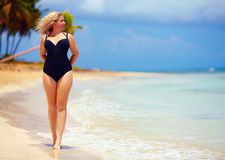 Beautiful plus size woman walking on summer beach. Holidays royalty free stock image