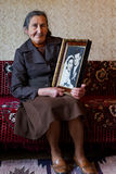 Beautiful 80 plus year old senior woman holding her wedding photograph. Love forever concept stock image