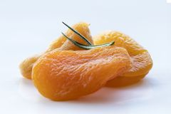 Beautiful and poetic photo of some orangy pretty dried apricot. Picture composed by dried apricots and rosemaries. High-angle shot. Seen from above. Close-up Royalty Free Stock Photo