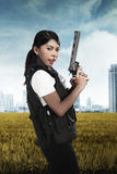 Beautiful police woman holding gun royalty free stock photography