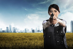 Beautiful police woman holding gun stock images