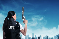 Beautiful police woman holding gun royalty free stock image