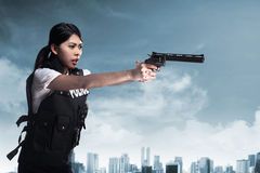 Beautiful police woman holding gun. Ready to fire Stock Image