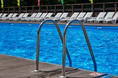 Beautiful pool with blue water under the open sky. The image is focused on the metal stairs railing Royalty Free Stock Photo