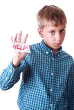 Beautiful poor boy in a blue shirt shows a message Help! Stock Photography