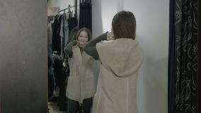 Beautiful popular woman shopping trying clothes in the fitting room and looking in the mirror -. Beautiful popular woman shopping trying clothes in the fitting stock video