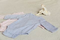Baby clothes. Beautiful Porcelain Figure of a Pretty Young Lady Ballet Dancer near a Baby clothes on a baby `s bed stock photography