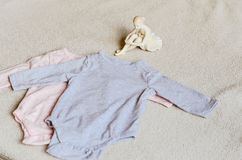 Baby clothes. Beautiful Porcelain Figure of a Pretty Young Lady Ballet Dancer near a Baby clothes on a baby `s bed royalty free stock photo