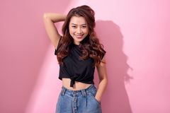 Beautiful portrait Asian cheerful young girl posing in casual clothes with beaming smile standing  on pink background.  stock image