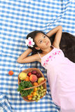 Beautiful portrait of Asian little girl. Little Asian beautiful girl lying at the cloth with full basket of summer fruits Royalty Free Stock Photo