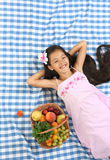 Beautiful portrait of Asian little girl. Little Asian beautiful girl lying at the cloth with full basket of summer fruits Stock Photography