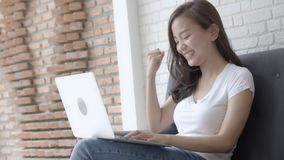 Beautiful portrait asian young woman working online laptop with smile and happy sitting on couch at living room stock footage