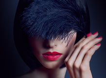 Fashion beauty portrait of brunette woman with black feather Royalty Free Stock Photos