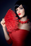 Fashion beauty portrait of brunette woman with red feather fan Stock Image