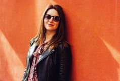 Beautiful portrait of brunette woman against wall in sunny day royalty free stock photography