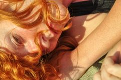 Beautiful portrait in closeup of a young elegant sexy red-haired curly woman on the beach full of love and desire stock image
