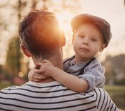 Beautiful portrait of a cute little boy hugging his dad royalty free stock images
