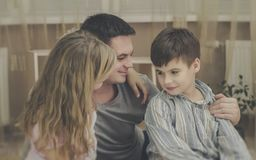 Beautiful portrait of a father with his to kids at home.  royalty free stock photography