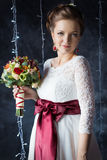 Beautiful portrait of a gentle cute happy bride in a white dress with a bright little colored bouquet Stock Photos