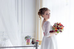 Beautiful portrait of a gentle cute happy bride in a white dress with a bright little colored bouquet. Beautiful portrait of a gentle cute happy bride in a white Stock Photos