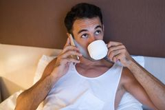 Beautiful portrait of handsome thoughtful young man using a mobi. Le phone and drinking cup of coffee in the white bed Stock Photo