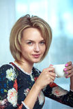 Beautiful portrait of happy blonde woman with mug Stock Photo