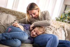 Beautiful portrait of a happy woman tickling a daughter in bed. Happy young women and her daughter having fun at home Stock Photos
