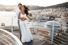Beautiful portrait of a just married young couple, poses embracing behind of a old city and sea port, during sunset. stock photography