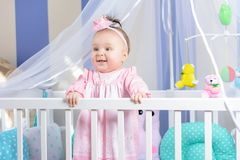 Beautiful portrait of a little girl in a pink dress in a nursery royalty free stock image