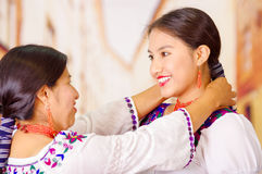 Beautiful portrait of mother with daughter, both wearing traditional andean clothes and matching necklaces, posing Stock Image
