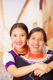 Beautiful portrait of mother with daughter, both wearing traditional andean clothes and matching necklaces, posing Royalty Free Stock Image