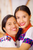 Beautiful portrait of mother with daughter, both wearing traditional andean clothes and matching necklaces, posing Royalty Free Stock Images