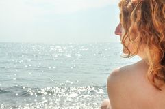 Beautiful portrait in profile closeup of a young red-haired curly woman by the sea on the beach in Italy with copy space, space royalty free stock photos