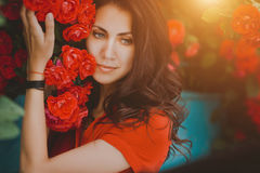 Beautiful portrait of sensual brunette woman close to red roses. Toned image Stock Photography