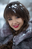 Close-up portrait of smiling,happy,beautiful,attractive girl with dark eyes,red lips,healthy white cute smile,snowflakes in hair. Beautiful portrait of cute Stock Images