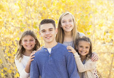 Beautiful Portrait of smiling happy kids outdoors. Four siblings standing together for a cute picture on a warm fall day Stock Photos