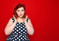Beautiful portrait of style and make-up, manicure, nails of the hands, red lipstick and polka-dot dress. She admires her hairstyle royalty free stock photography