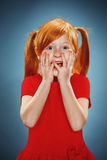 Beautiful portrait of a surprised little girl. The beautiful portrait of a  surprised little girl with red hair in red dress on blue Stock Images