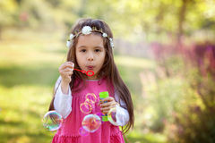 Beautiful portrait of sweet lovely little girl blowing soap bubb Stock Photography