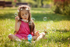 Beautiful portrait of sweet lovely little girl blowing soap bubb Stock Image