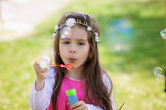 Beautiful portrait of sweet lovely little girl blowing soap bubbles royalty free stock photos