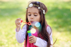 Beautiful portrait of sweet lovely little girl blowing soap bubb Royalty Free Stock Photography