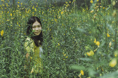Beautiful portrait of young asain woman in yellow flowers garden Royalty Free Stock Photo