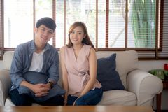 Beautiful portrait young asian couple relax and satisfied together in living room at home, family sitting couch. Confident with cheerful and happy with stock photos