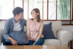 Beautiful portrait young asian couple relax and satisfied together in living room at home, family sitting couch. Confident with cheerful and happy with stock image