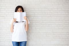 Beautiful portrait young asian woman happy hiding behind open th. E book with cement or concrete background, girl standing reading for learning, education and royalty free stock photography