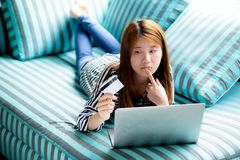Beautiful of portrait young asian woman lying think use credit c. Ard with laptop, Content girl shopping online and payment with notebook computer on sofa stock image