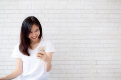 Beautiful of portrait young asian woman touch phone and smile st. Anding on cement brick background, freelance female calling telephone, communication concept stock photos