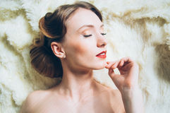 Beautiful portrait of young girl in retro style. On fur, closed eyes Stock Photos