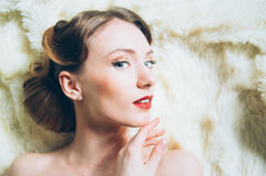 Beautiful portrait of young girl in retro style. On fur, looking to the camera Royalty Free Stock Image